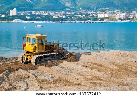 The preparation of the beach for the summer season, a bulldozer equal shingle beach - stock photo