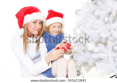 The pretty girl and her mother with  gift box are sitting near Christmas tree on a white background.