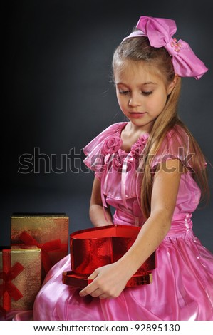 The pretty girl in a pink dress a gift-heart in hands