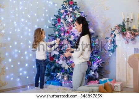 The pretty girl with mum are decorating a Christmas tree in the house. Happy family. Merry Christmas and New Year. - stock photo