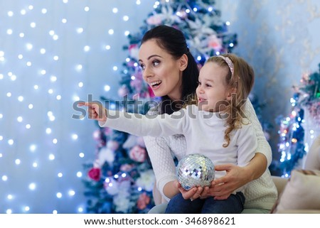 The pretty girl with mum sitting near Christmas tree in the house. Happy family. Merry Christmas and New Year. - stock photo