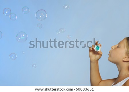 The pretty girl with soap bubbles. A  blue background