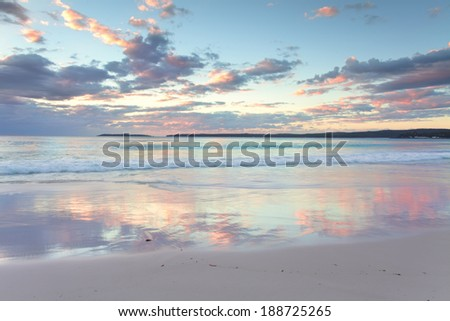 The pretty pastel colours of dawn sunrise and reflections in the water at Hyams Beach South Coast of NSW Austalia.  A wonderful way to clear the mind and start the day - stock photo