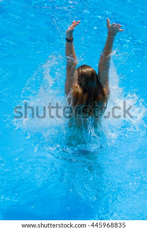 The pretty young woman splashes in a swimming pool