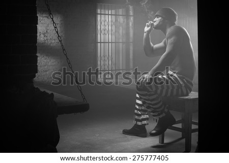 The prisoner worries about a criminal conduct being behind a lattice - stock photo