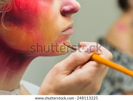 The process of applying color to the face makeup on model. Makeup artist  apply makeup on the model's face special makeup brushes. Makeup artist at work. - stock photo