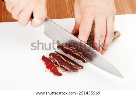 the process of cutting the dried beef on cutting board closeup - stock photo