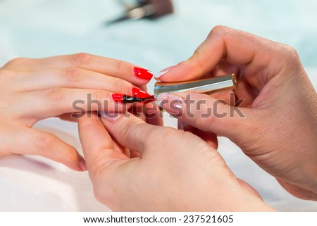 The process of doing a manicure in the spa salon. Applying red nail polish on the nails in the nail salon. Manicure, hand care, nail care, red lacquer. The concept of hand care, nail beauty. - stock photo