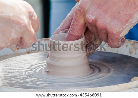 The process of manufacture of arms and training on the machine pottery - stock photo