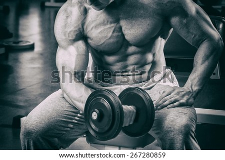 The process of physical exercise with dumbbells. The man is engaged in the gym. Training in the gym. Healthy lifestyle. Photo in creative.