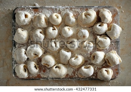 The process of preparation of Russian meat dumplings. Homemade raw dumplings with flour on a wooden board. View from above. - stock photo