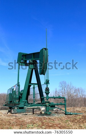 The pump jack on field in spring, USA, Ohio - stock photo