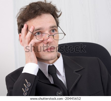 The puzzled young man - businessman in points - stock photo