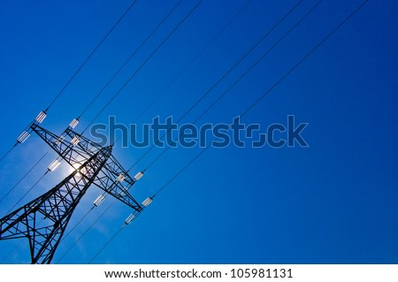 the pylons of a power line with sun and blue sky - stock photo
