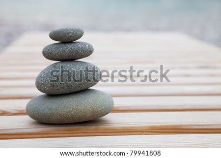 The pyramid of pebbles on a wooden background - stock photo
