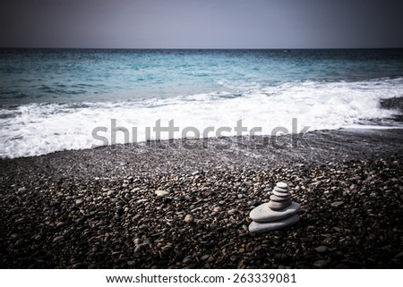 The pyramid of pebbles on the beach in sea foam. - stock photo
