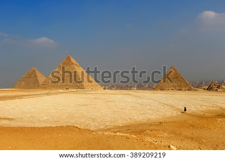The Pyramids of Giza, man-made structures from Ancient Egypt in the golden sands of the desert with polluted Cairo in the background  - stock photo