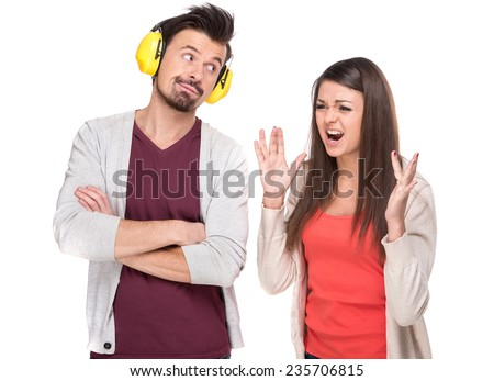 The quarrel between the young couple. Man with headphones while she screams. - stock photo