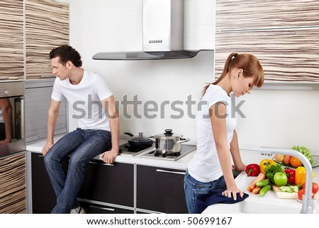 The quarrelled young married couple at kitchen - stock photo