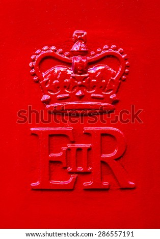 The Queen Elizabeth Royal Crest on a red Post Box in the United Kingdom. - stock photo