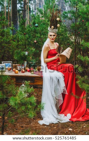 the Queen of Christmas . slim girl in red dress posing in the spirit of the snow Queen , a fairy-tale image of Christmas in the woods . populates the list of good and bad children who will receive