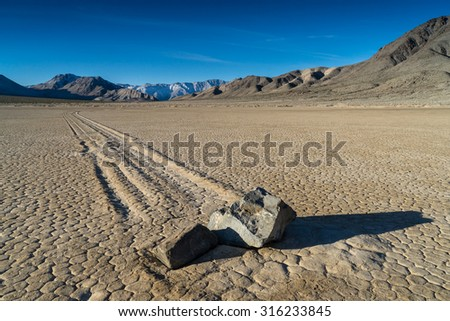 """The Racetrack Playa, or The Racetrack, is a scenic dry lake with """"sailing stones"""" that inscribe linear """"racetrack"""" imprints. It is located in Death Valley National Park, Inyo County, California, U.S. - stock photo"""