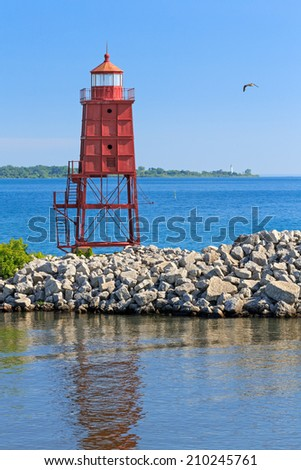 The Racine, Wisconsin North Breakwater Lighthouse is backed by the lighthouse at Wind Point on the distant horizon. - stock photo