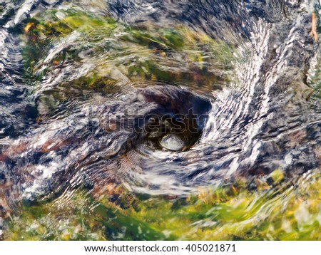 The raging whirlpool on surface of the deep river in blur the background - stock photo