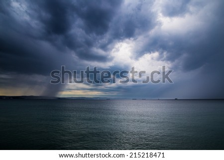 The rain on the sea in front of the city - stock photo