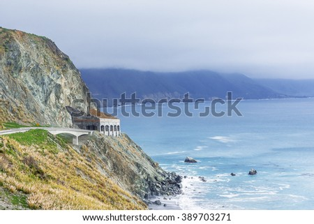The Rain Rocks Rock Shed & Pitkins Curve Bridge with aquamarine waters, during an El Nino storm, along the rugged Big Sur coastline, near Carmel and Monterey, CA. on the California Central Coast. - stock photo