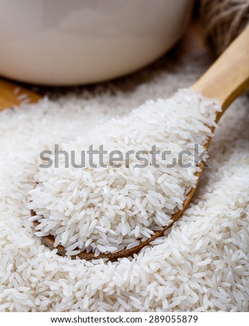 The raw white rice on the wooden spoon