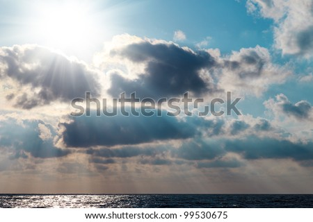 The rays of the sun breaking through clouds over the sea - stock photo