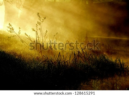 The rays of the sun in the fog by a pond near the Museum of Yanka Kupala. Minsk, Belarus. - stock photo