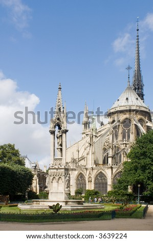 The rear side of the Notre Dame Cathedral in Paris with it's beautiful and tranquil garden, just catching the sunlight. The blue sky can very well be used as copyspace - stock photo