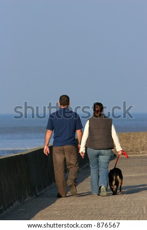 The rear view of a couple walking their dog on a promenade. - stock photo