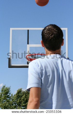 The rear view of a young boy facing a hoop as a basketball ascends toward it. Horizontally framed shot. - stock photo