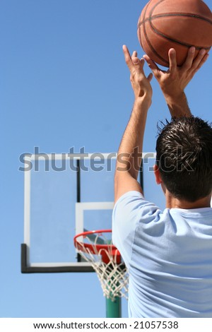 The rear view of a young boy shooting a basketball toward a hoop. Vertically framed shot. - stock photo