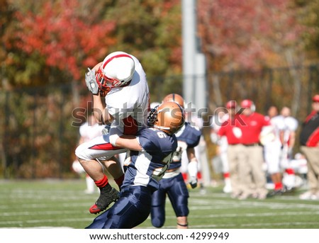 The receiver makes a leaping catch over the defensive back for a touchdown. - stock photo