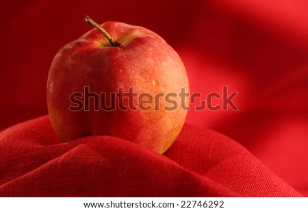 The red apple lays against a red fabric
