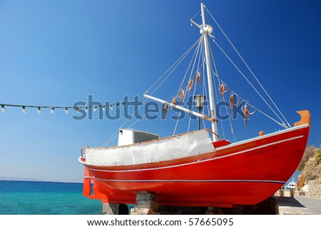 The red boat with octopus on the island of Mykonos, greek colours - stock photo