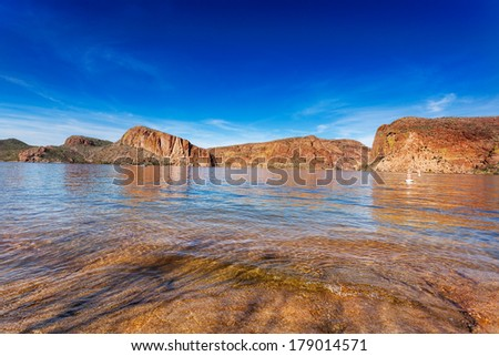 The red cliffs surrounding Canyon Lake, reflected in the calm waters on a sunny Winter afternoon - stock photo