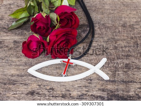 The red cross  over the white christian fish and red roses  on wooden background, world mission concept.  - stock photo