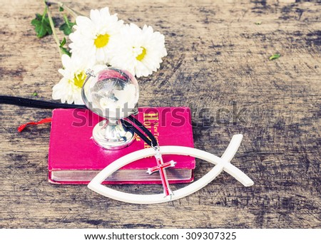 The red cross  over the white christian fish and the world globe model on the red bible with white flowers on wooden background, world mission concept.  - stock photo