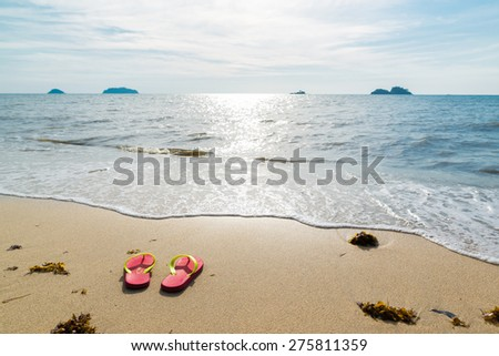 The red flip-flops on the beach in summer.