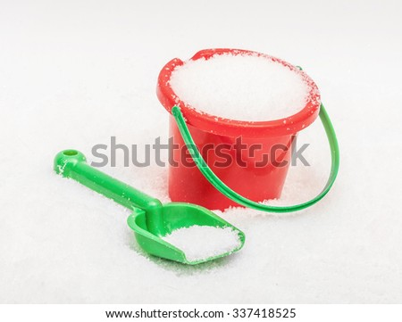 The red green bucket and shovel which are filled up with snow, covered snow - stock photo
