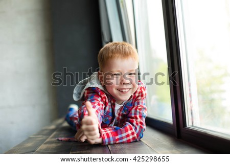 the red-haired boy is lying on the windowsill cheerful and happy Red head boy with freckles looking shocked and surprised while smiling and holding hands in air - stock photo