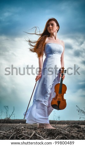 The red-haired girl with a violin outdoor - stock photo