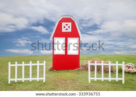 The red house  on a green lawn  trees and white fence ,and beautiful sky and cloud background - stock photo