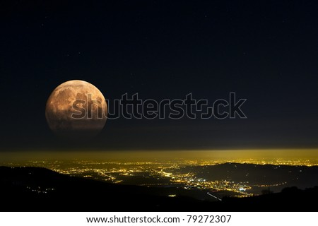 The red Moon rises over city lights. - stock photo