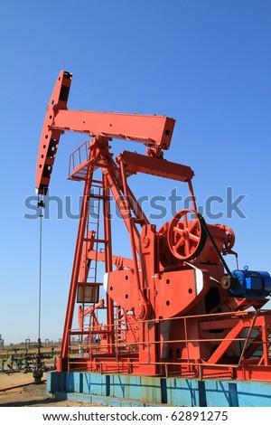The red oil pump jack on blue sky - stock photo